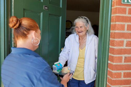 Young person handing senior a meal at their front door